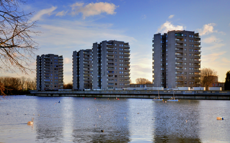 A lake in the foreground with small waterfowl and two boats. Four highrise tower blocks stand in the background.